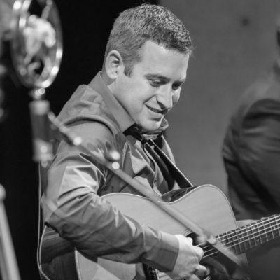 Black and white photo of Dan Boner playing the guitar