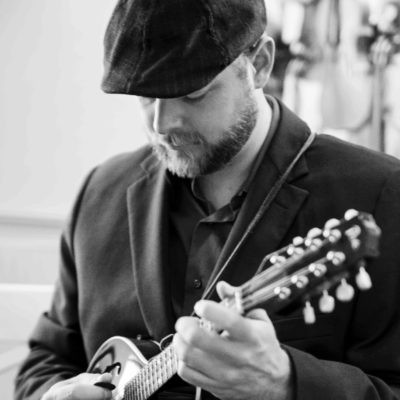 Black and white photo of Nate Lee playing the mandolin